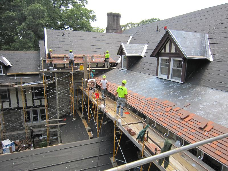 GSM workers installing clay tiles at Cabrini College Mansion roof restoration project.