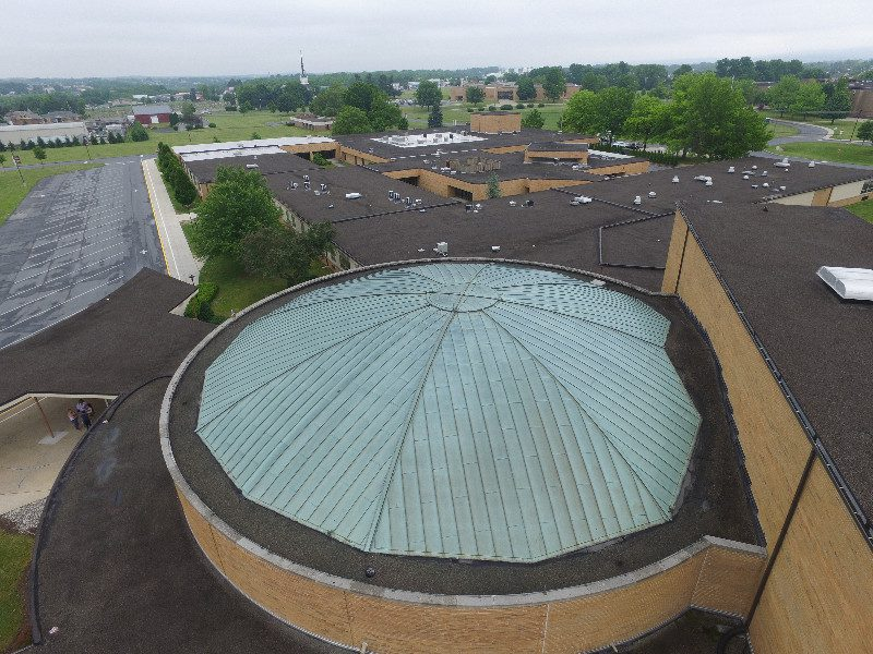 high school dome roof with hail damage
