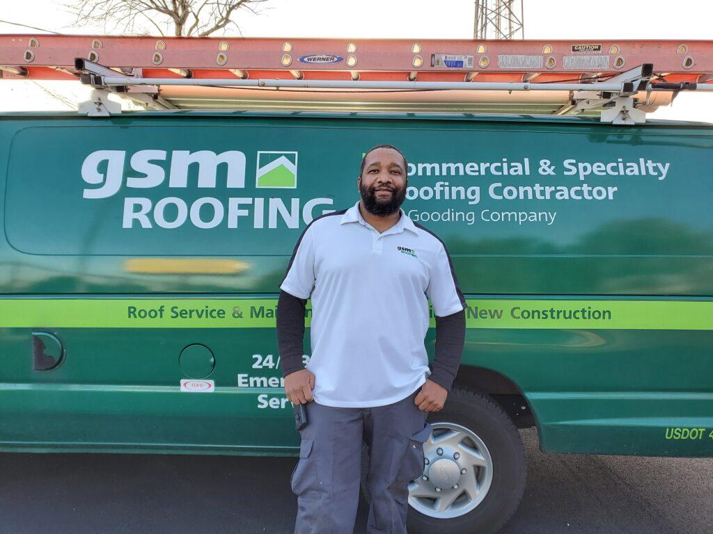 Joel Mondesir standing in front of a GSM Roofing van